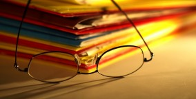 Reading glasses on pile of files
