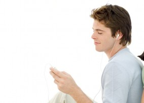 Young Man Listening to Music with Headphones --- Image by © Royalty-Free/Corbis