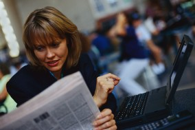 Businesswoman With Laptop Reading Newspaper